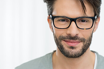 Man Smiling with New Black Glasses