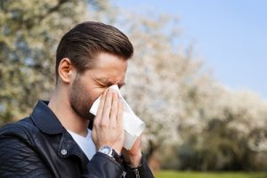 man with allergies using tissue
