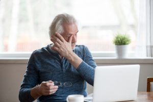 man wiping his eyes while on laptop