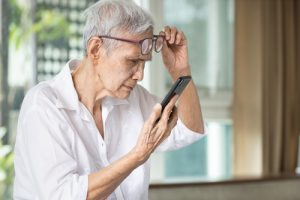 older woman trying to read cell phone